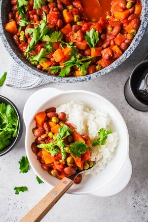 Vegan bean stew with tomatoes and rice in a pan over white background. Vegan food concept.