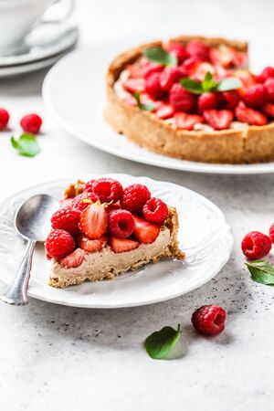 Vegan berry tart with raspberries, strawberries and cream on a white plate.