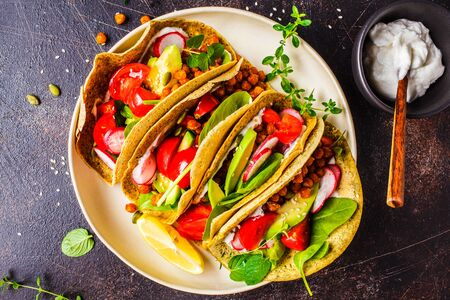 Vegan tacos with baked chickpeas, avocado, sauce and vegetables on a dark background.
