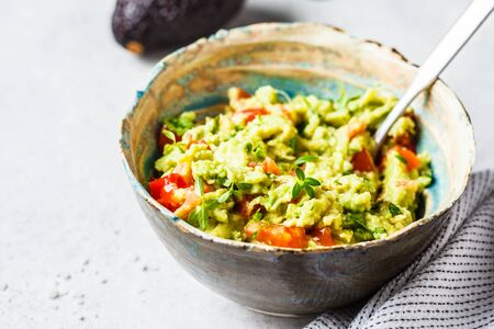 Fresh avocado tomato guacamole in a bowl. Healthy vegan food concept.