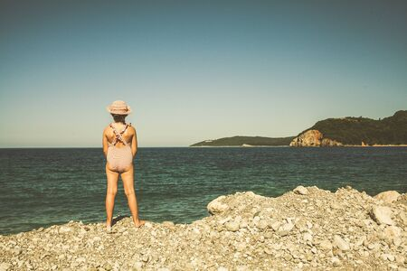Girl child in a bathing suit standing on the beach. Montenegro beach.