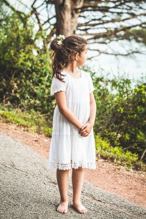Beautiful barefoot girl in white dress standing near the mountain.