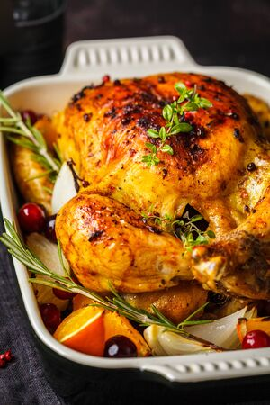 Baked chicken with spices and onions in a glass dish.