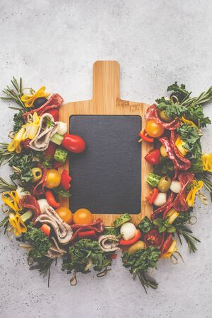 Christmas food background. Christmas festive snack on a serving chalkboard, white background, top view.