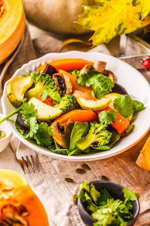 Autumn salad from baked pumpkin, beet, zucchini and carrots. Healthy vegan food concept. Autumn food concept.