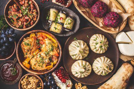 Tło tradycyjnej kuchni gruzińskiej. Chinkali, phali, chahokhbili, lobio, ser, bułki z bakłażana na ciemnym tle, widok z góry.
