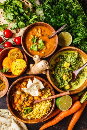 Food traditional Indian cuisine. Dal, palak paneer, cheese balls, curry, rice, chapati, chutney in wooden bowls on dark background. 版權商用圖片
