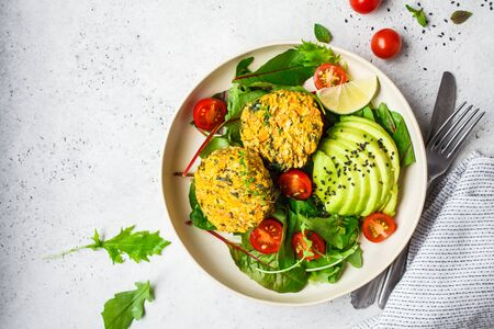 Vegan vegetable burgers with salad in a white plate, copy space.