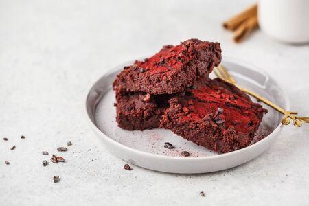 Veganer Brownie der Roten Beete auf grauem Teller. Gesundes veganes Lebensmittelkonzept.