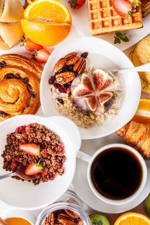 Breakfast table with oatmeal, granola, waffles, croissants and fruits. White background. Stock Photo