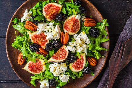 Salad with figs, feta cheese and blackberries in a wooden plate on a dark background.