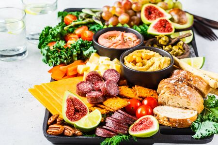 Meat and Cheese appetizer Platter. Sausage, cheese, hummus, vegetables, fruits and bread on a black tray, white background. Reklamní fotografie - 129165506