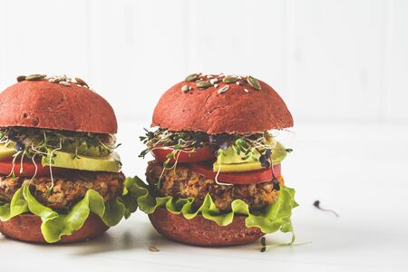 Pink vegan burgers with beans cutlet, avocado and seedlings on a white background.
