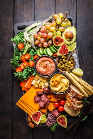 Meat and Cheese appetizer Platter. Sausage, cheese, hummus, vegetables, fruits and bread on a black tray, dark background. Stock fotó