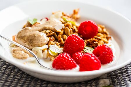 Healthy vegan breakfast - baked oatmeal crumble with berries and nut butter in white plate. Stock Photo - 129419266