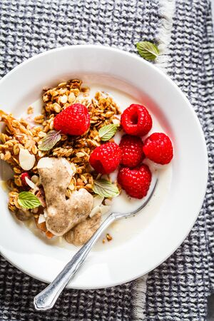 Healthy vegan breakfast - baked oatmeal crumble with berries and nut butter in white plate.