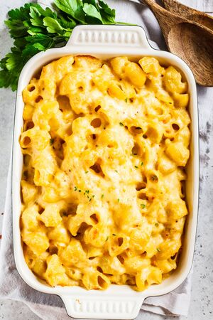Mac and cheese in the oven dish, white background, top view.
