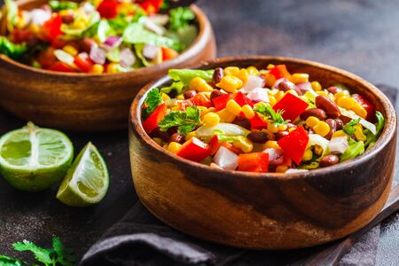 Traditional corn bean mexican salad in wooden bowl, dark background. Mexican food concept. Stock Photo