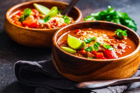 Traditional mexican bean soup with meat and cheese in a wooden bowl. Mexican food concept. Stockfoto