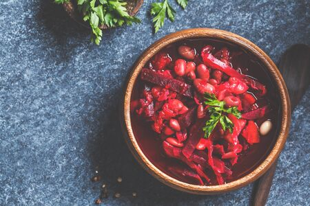 Vegetarian beetroot soup borsch with beans in a wooden bowl on a blue background. Healthy vegetarian food concept.