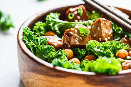 Teriyaki tofu salad with kale and chickpeas in wooden bowl.