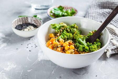 Vegan stew with chickpeas, sweet potato and kale in a white bowl. Archivio Fotografico - 131354171