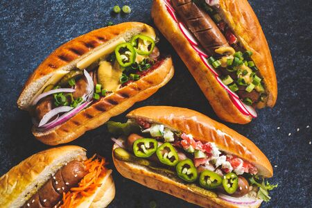 Hot dogs with different toppings on a dark blue background, food flat lay. Fast food concept.