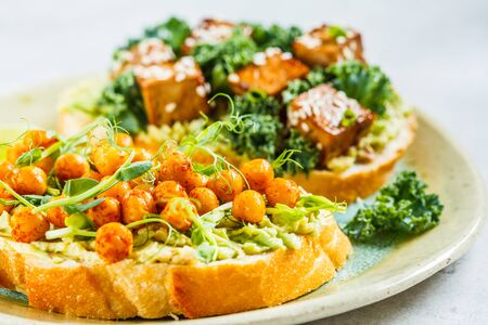Vegan open sandwiches with guacamole, tofu, chickpeas and sprouts on a plate. Healthy vegan food concept. Stockfoto
