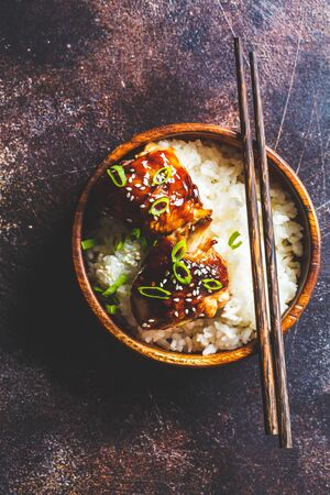 Teriyaki chicken with rice in a wooden bowl, dark background.