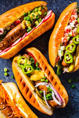 Hot dogs with different toppings on a dark blue background, food flat lay. Fast food concept. Stockfoto