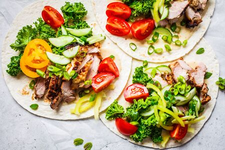 Healthy mini tortillas with grilled chicken, meat, sauce, fresh vegetables  on light grey background, top view. Healthy food picnic concept.