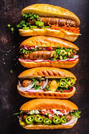 Perritos calientes con diferentes ingredientes sobre un fondo oscuro. Concepto de comida rápida.