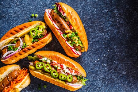 Hot dogs with different toppings on a dark blue background. Fast food concept. Stockfoto