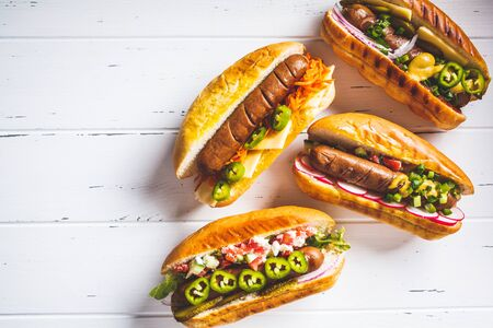 Hot dogs with different toppings on a white background. Fast food concept.