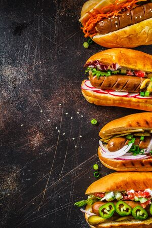 Hot dogs with different toppings on a dark background. Fast food concept.