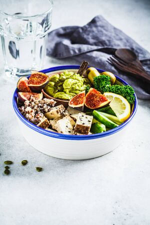 Buddha bowl with quinoa, tofu, kale, figs and guacamole hummus in a white plate.