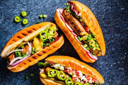 Hot dog con diversi condimenti su uno sfondo blu scuro, cibo piatto disteso. Concetto di fast food.