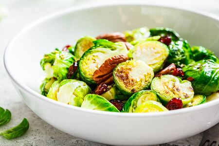 Roasted Brussels sprouts salad with cranberries and nuts in a white bowl. Healthy vegan food concept.