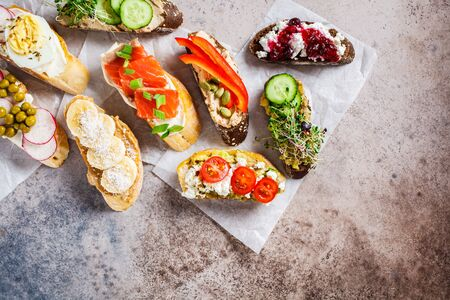 Open toasts with different toppings on gray-brown background.  Flat lay of crostini with banana and peanut butter, pate, avocado, salmon, egg, cheese and berries. Stock Photo - 132958241