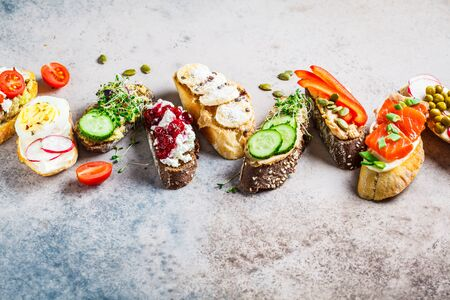 Open toasts with different toppings on gray-brown background, copy space.  Flat lay of crostini with banana and peanut butter, pate, avocado, salmon, egg, cheese and berries. Stock Photo