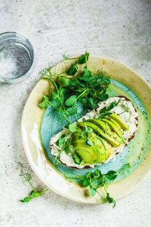 Rye bread toast with cream cheese and avocado on a beautiful plate. Healthy breakfast concept. Stock Photo