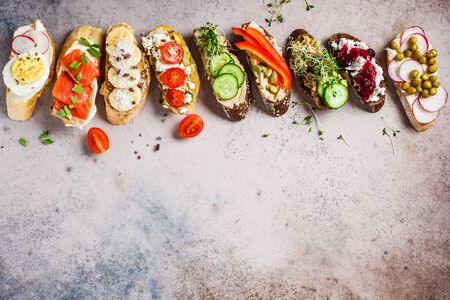 Open toasts with different toppings on gray-brown background.  Flat lay of crostini with banana and peanut butter, pate, avocado, salmon, egg, cheese and berries.