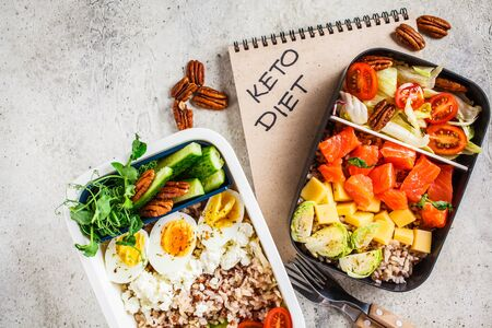 Lunch boxes with keto diet food, top view. Rice with fish, cheese, eggs and vegetables in food containers.