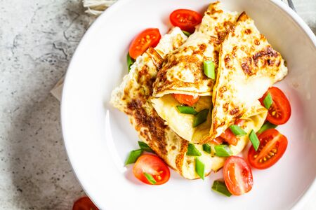 Omelet with salmon, cheese and green onions on a white plate. Keto diet menu concept. Stock Photo