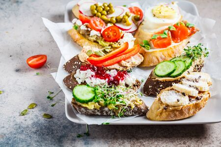 Open toasts with different toppings on gray-brown background, copy space.  Crostini with banana and peanut butter, pate, avocado, salmon, egg, cheese and berries.