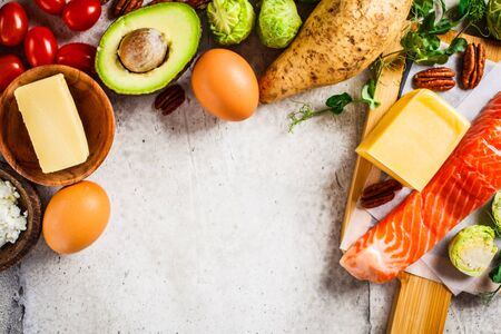 Keto diet food concept. Fish, eggs, cheese, nuts, butter and vegetables - ingredients keto diet, top view. Stock Photo - 132958259