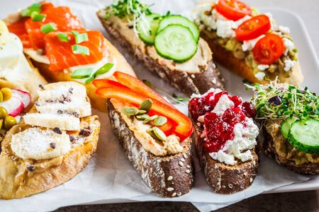 Open toasts with different toppings on gray-brown background. Crostini with banana and peanut butter, pate, avocado, salmon, egg, cheese and berries.