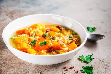 Soupe de légumes végétarienne aux lentilles et citrouille dans une assiette blanche.