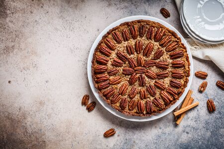 Whole pecan Pie on gray-brown background. Vegan dessert concept. Stock Photo - 133297277