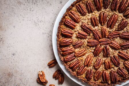 Whole pecan Pie on gray-brown background. Vegan dessert concept. Stockfoto